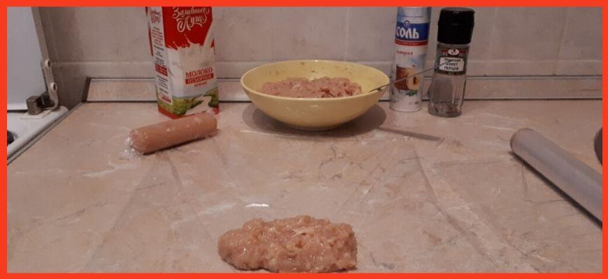 3.Теперь формируем сосиски. На отрезок пищевой плёнки выкладываем немного полученного фарша и плотно сворачиваем колбаской. С двух сторон плёнку завязываем ниткой, либо хорошо закручиваем края плёнки.